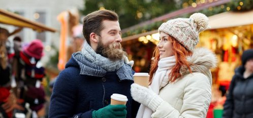 couple enjoying the holidays together laughing and drinking a warm cup of cocoa