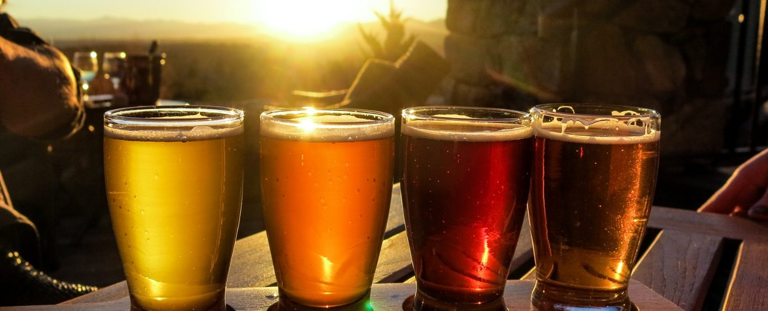 flight of beers outside at a brewery