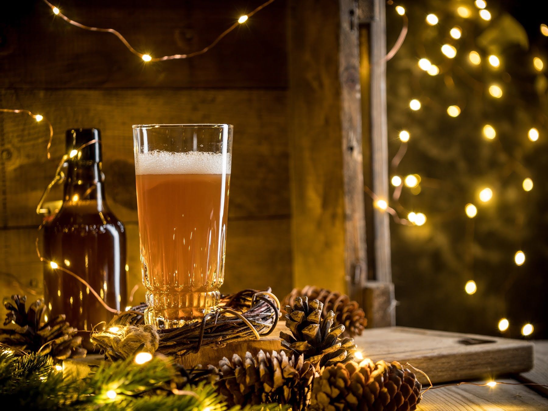 Beer in glass on wooden background with Christmas lights and pine cones
