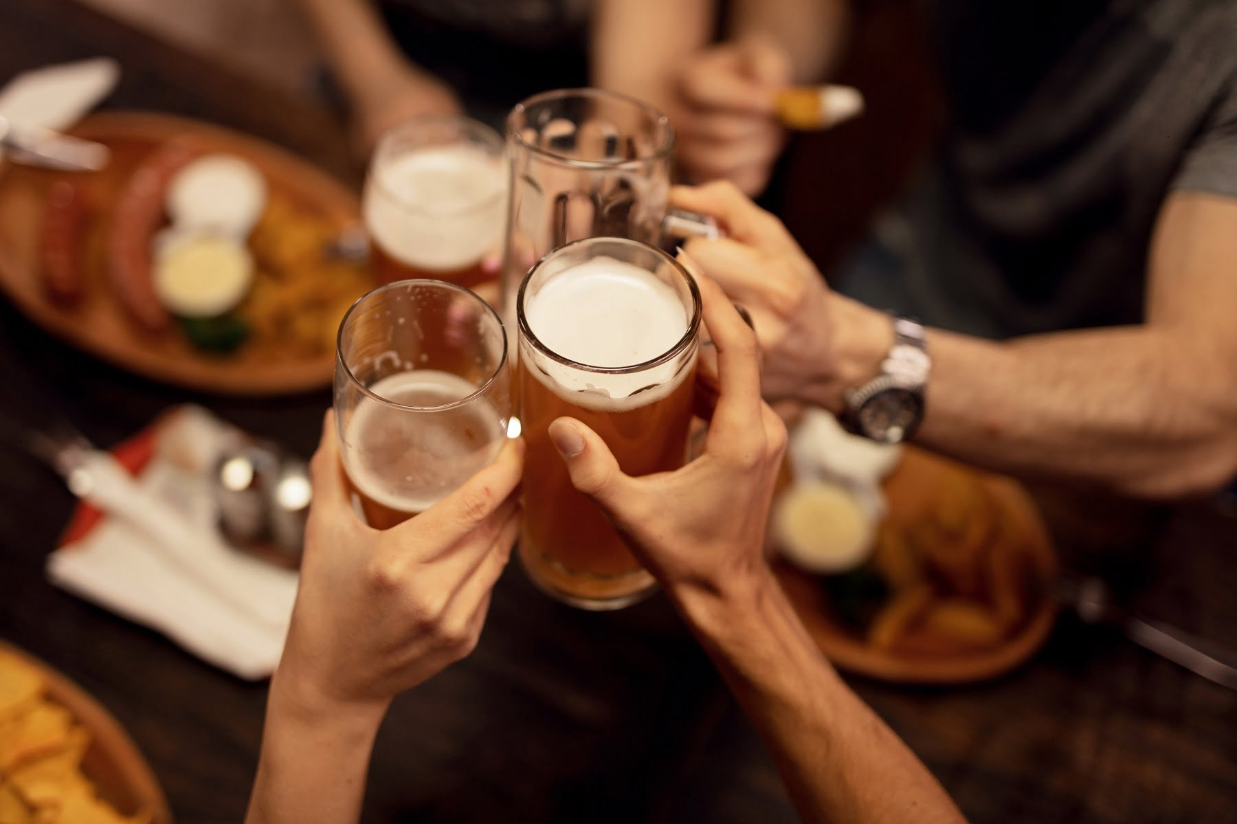 Close up of friends toasting with beer and having fun in a pub.