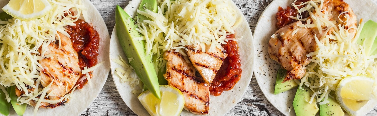 Grilled chicken, avocado, cheese and spicy tomato sauce tortillas on wooden rustic background, top view